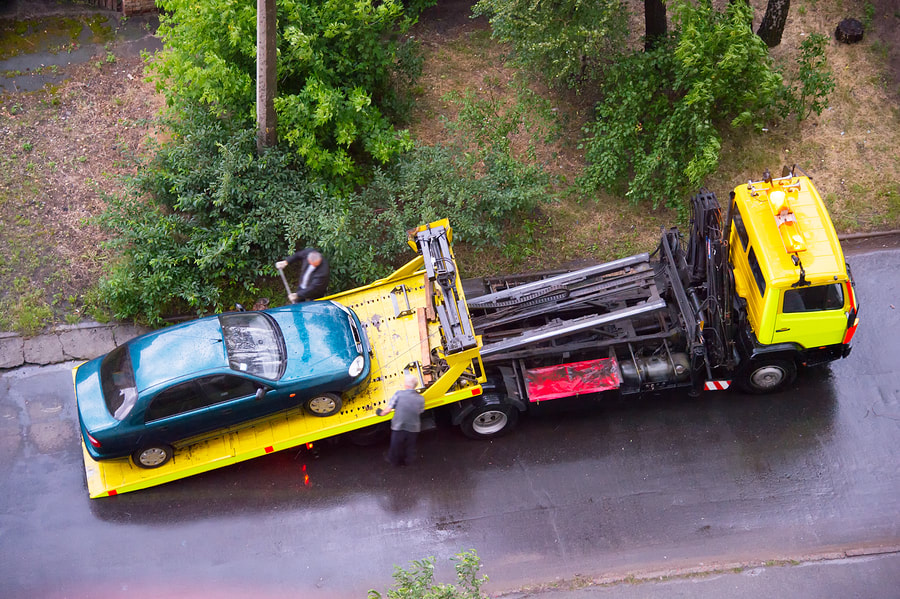 blue car being towed by the yellow towing truck