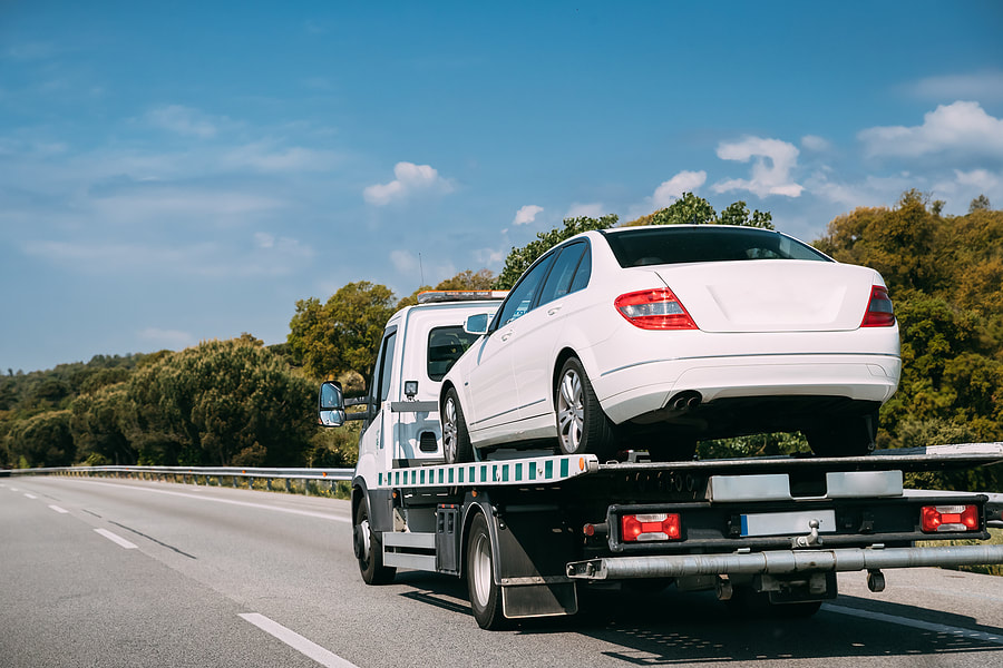 white car on a towing truck