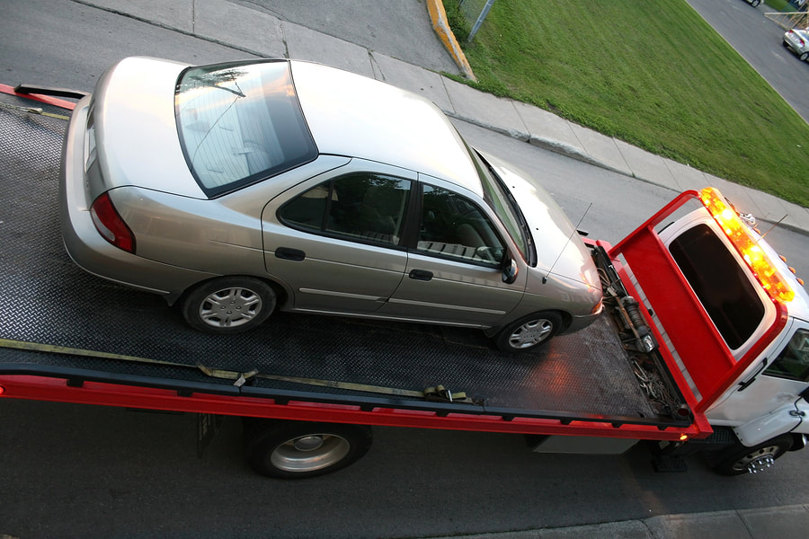 silver car towed by a towing truck